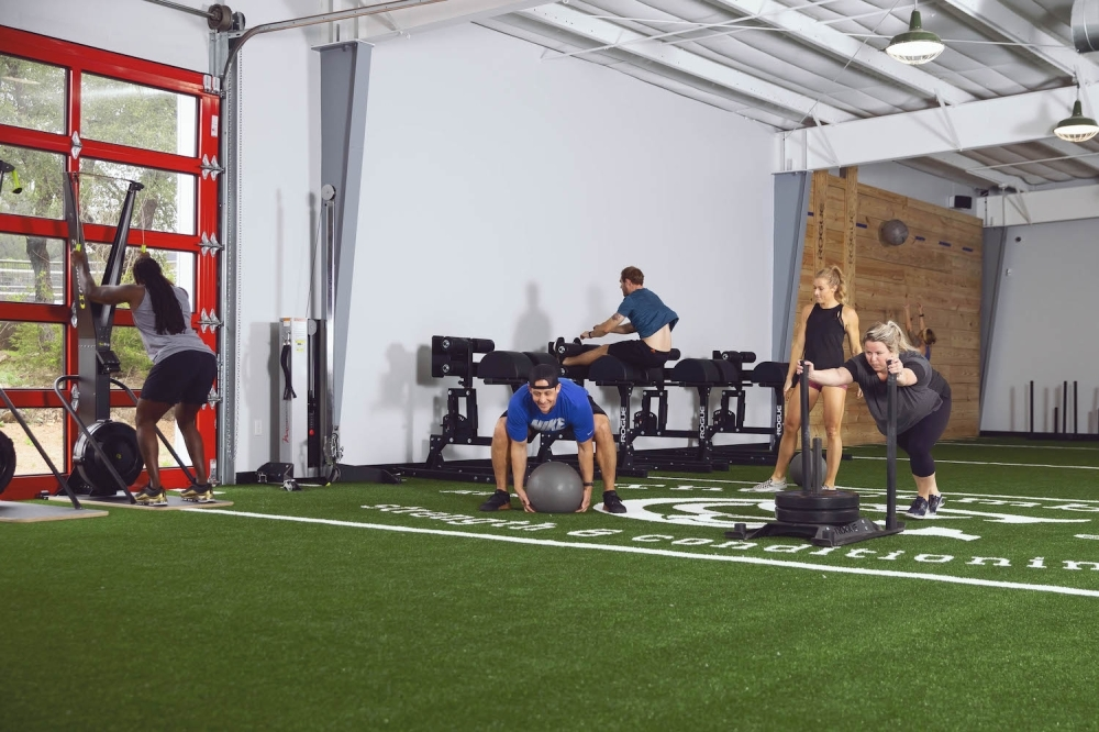A photo of several people exercising on indoor turf.
