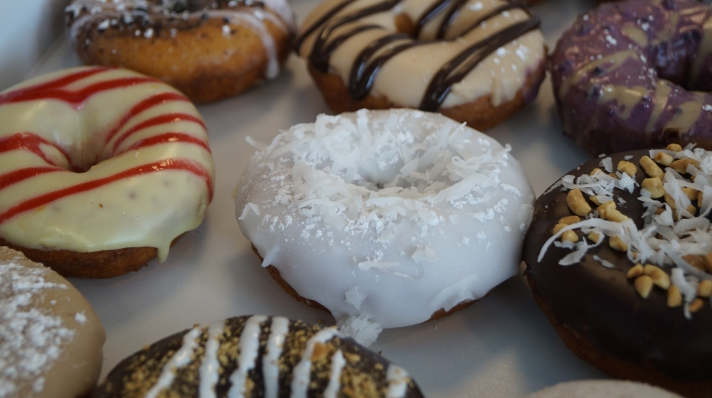 Classic toppings available at Duck Donuts include chocolate icing, blueberry icing, coconut, maple bacon, raspberry drizzle and more. (Kelsey Thompson/Community Impact Newspaper)
