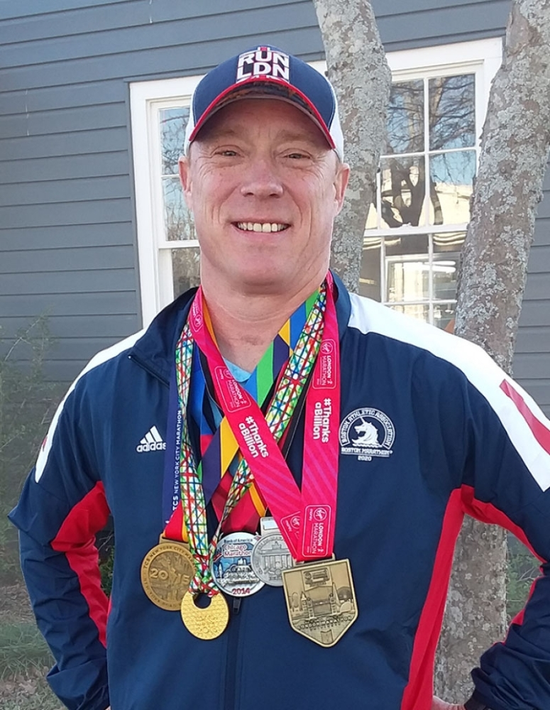 Leander's Ray Sterriker wears his five medals that are part of the marathon series. (Brian Perdue/Community Impact Newspaper)