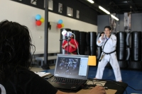 Co-owner and instructor Paul Resurreccion leads a virtual martial arts lesson online, while his wife, Hazel, manages the chat room. (Adriana Rezal/Community Impact Newspaper)