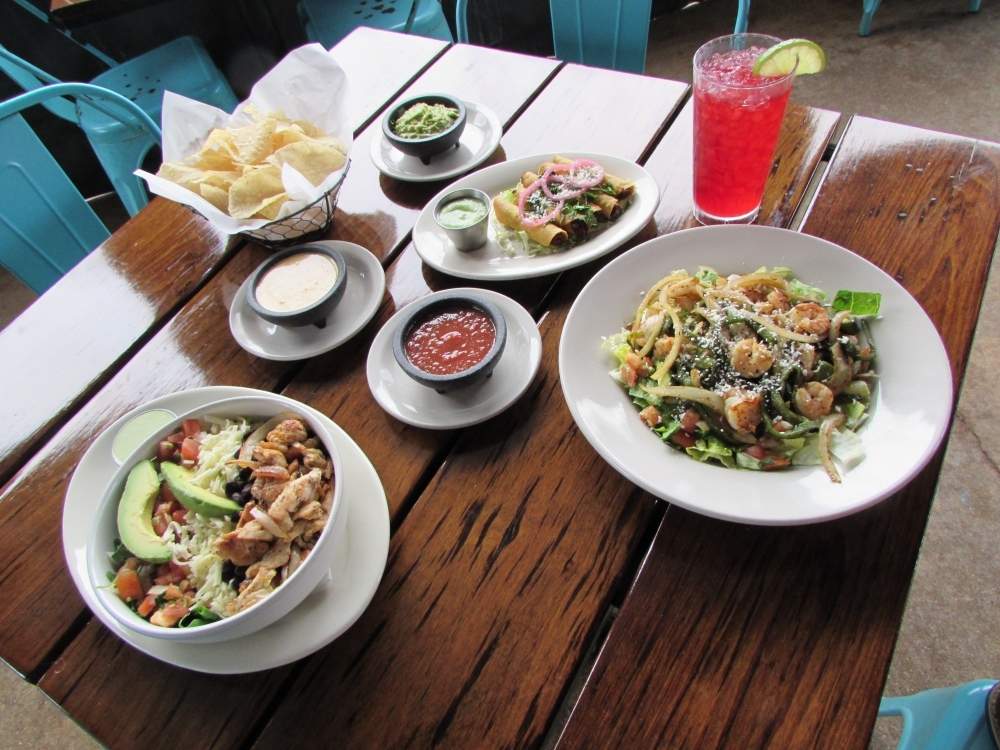 A table setting includes a Powerbowl; a Skinny Maida's Salad; Flautitas De Pollo; and chips with salsa, queso and guacamole. (Nicholas Cicale/Community Impact Newspaper)