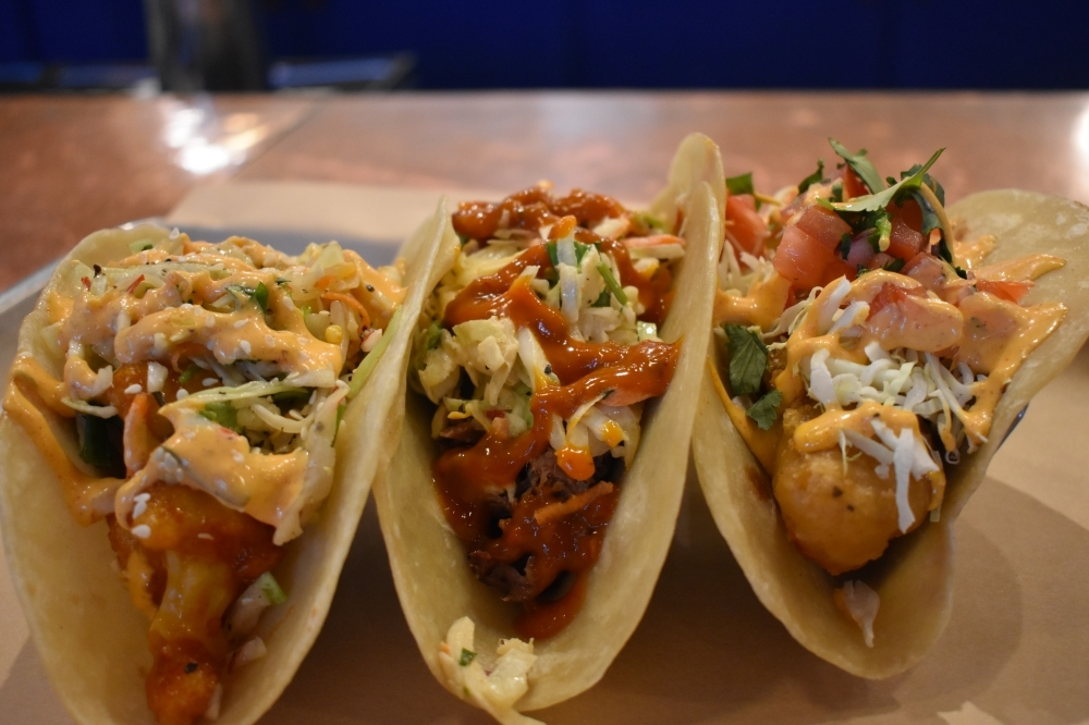 (From left to right) The Korean cauliflower taco is made with Gochujang sauce, Mojo sauce, ginger slaw and toasted sesame seeds.  The Brisket taco is made with smoked brisket, guajillo barbecue sauce and chipotle slaw. The Baja fish taco is made with beer-battered cod, shredded cabbage, pico de gallo and Mojo sauce. All tacos are $4. (Alex Hosey/Community Impact Newspaper)