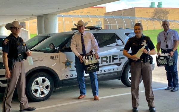 Deputy Nick Noel, Sheriff Jim Skinner, Sgt. Jessica Pond and Asst. Chief Anthony Carter of the Collin County Sheriff's Office show off the hospital-grade disinfectant they received as part of the Facebook group created by The Cleaning Force. (Courtesy Collin County Sheriff's Office)