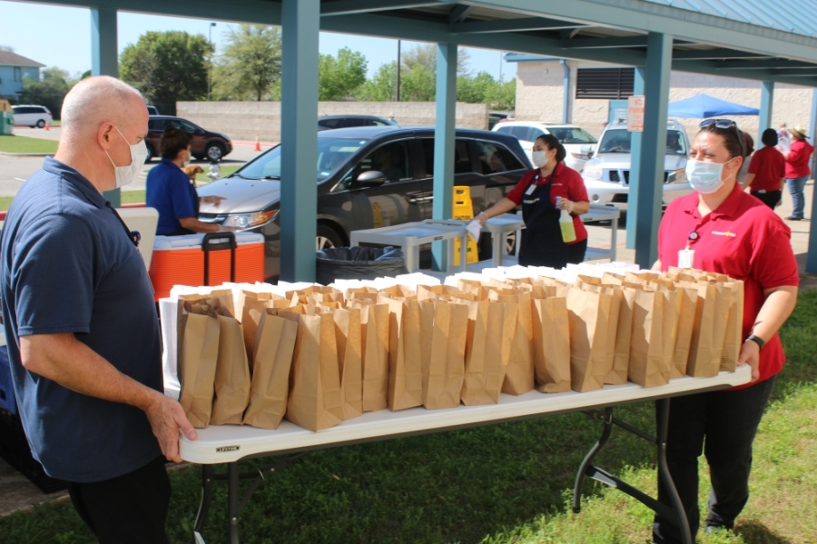 Leander ISD child nutrition services employees carry out a table of lunches at Bagdad Elementary School in Leander on March 25. (Brian Perdue/Community Impact Newspaper)