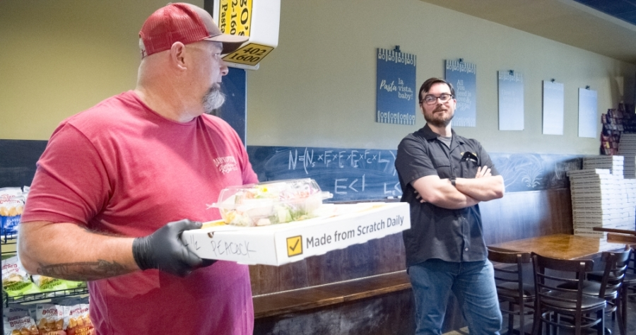 CraigO's Pizza & Pastaria owner Andrew Rincon (right), volunteer Mark Crowell (left) and a team of several other people helped feed dozens of at-risk families in the Lake Travis community April 2. (Courtesy Mason Culp)