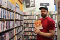 A photo of a man in a red shirt and black hat standing in a video rental store