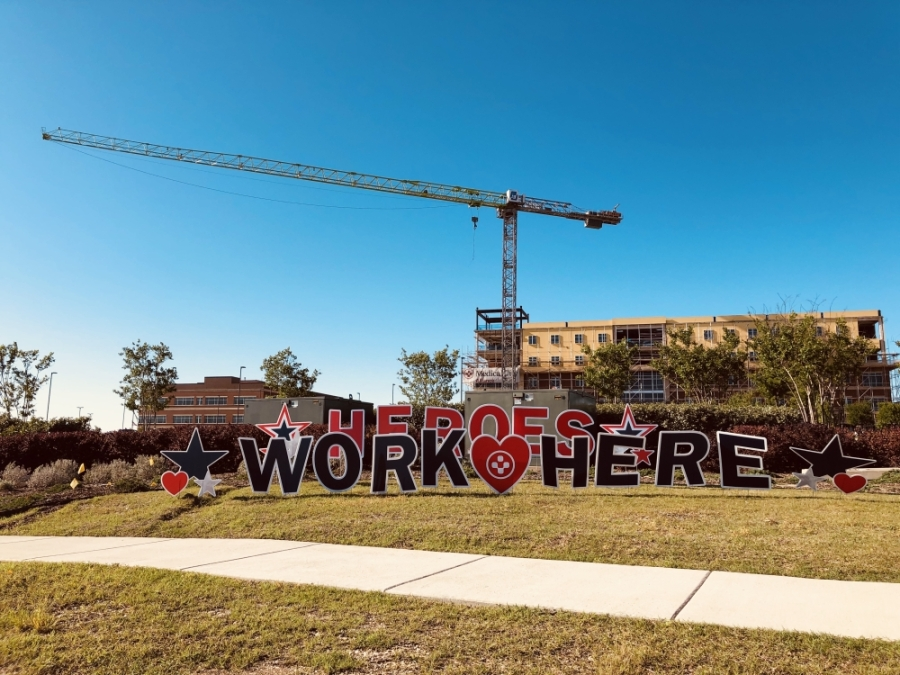"Colorful yard signs decorate the roadside near Medical City Alliance hospital. The signs spell out, ""Heroes Work Here."" (Ian Pribanic/Community Impact Newspaper)"