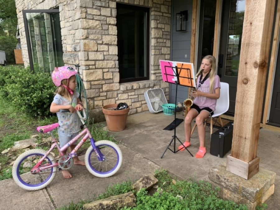 Sycamore Springs Middle School student Brooklynn Allen performs a porch concert, with her younger sister a captive audience. (Courtesy Dripping Springs ISD)
