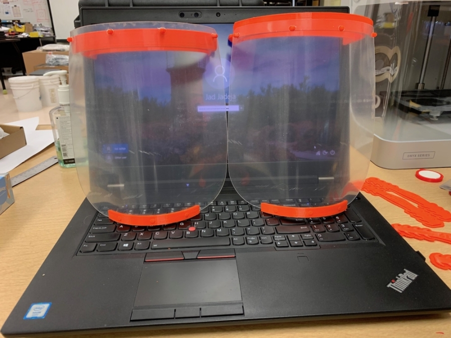 A photo of two clear face shields sitting atop a black laptop computer