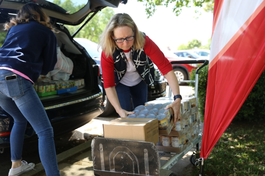 Mimi Conner (right) unloads food from her car after picking up non-perishable foods from the North Texas Food Bank and purchasing foods from Aldi, with help from volunteer Michelle Leavitt. (Liesbeth Powers/Community Impact Newspaper)