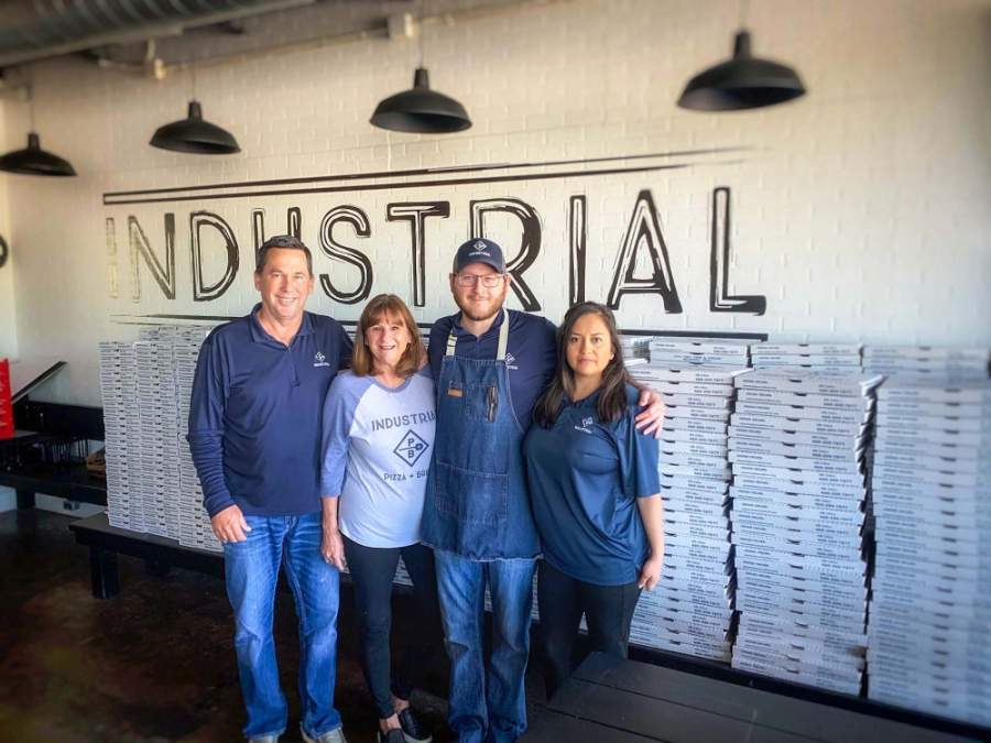 Industrial Pizza + Brew has embraced takeout and curbside pickup following the statewide ban on dine-in service. From left are owners Kelly and Becky Newsom and son and daughter-in-law Hunter and Mariana Newsom. (Courtesy Industrial Pizza + Brew)