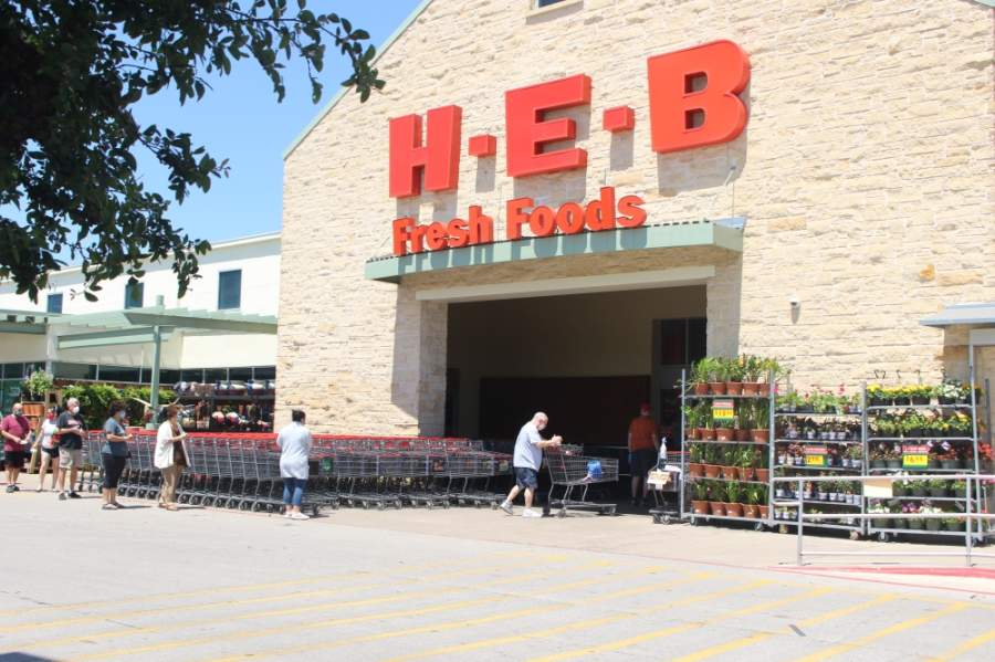 Southwest Austin residents wearing medical masks wait in line to enter the H-E-B on the corner of Brodie Lane and William Cannon Drive April 16. (Nicholas Cicale/Community Impact Newspaper)