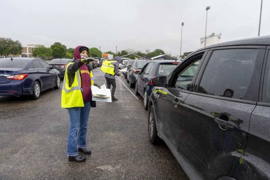 A Central Texas Food Bank volunteer directs traffic during a food drive at Nelson Field on April 4. (Courtesy Central Texas Food Bank)