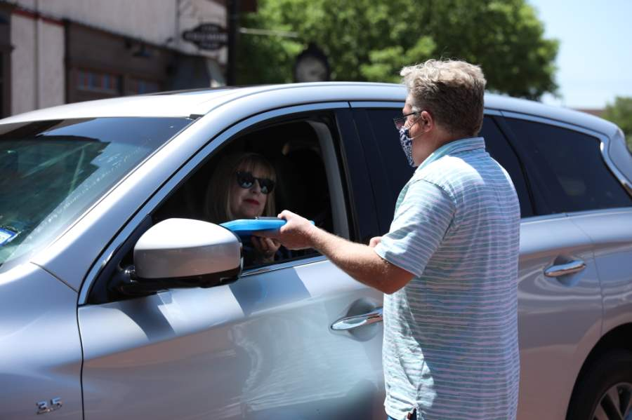 Michael Hamilton, owner of La Foofaraw, finishes up a curbside pickup transaction in downtown Plano April 24. (Liesbeth Powers/Community Impact Newspaper)