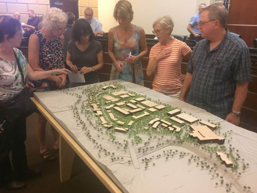 Residents examine a model of the Village at Spanish Oaks during an August 2018 Bee Cave City Council meeting. (Brian Rash/Community Impact Newspaper)