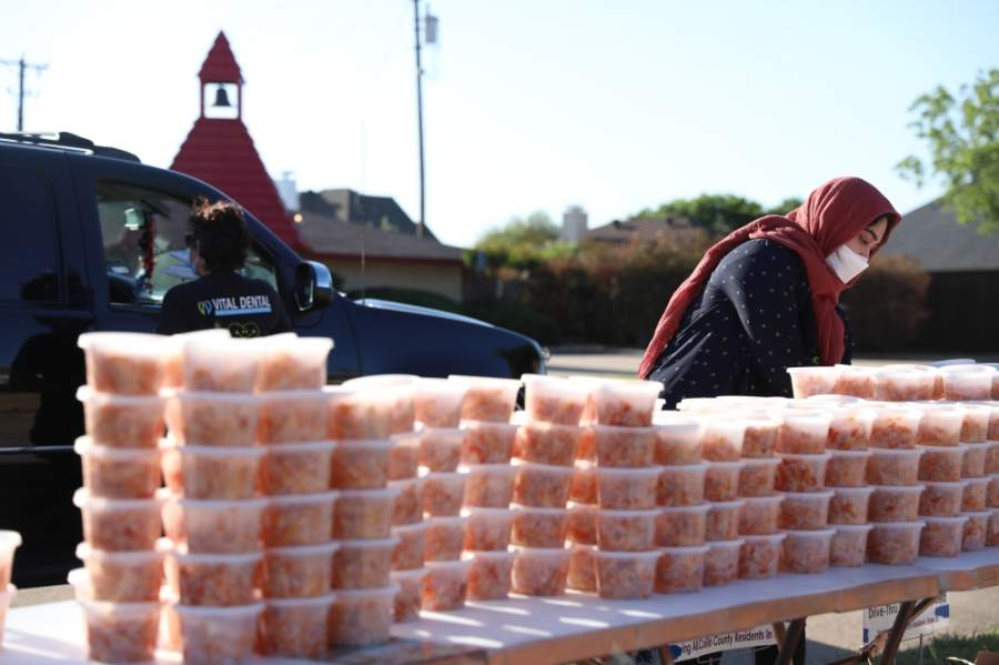 Noreen Choudhury, a volunteer with In-Fretta, gathers meals for a family outside of Allen Community Outreach. (Liesbeth Powers/Community Impact Newspaper)