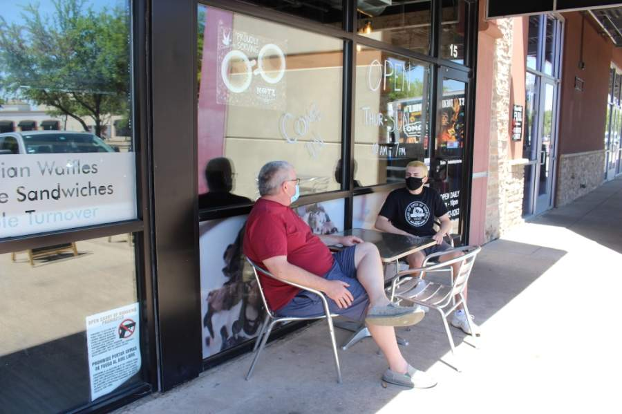 Father and son Tom and Max Brunell wait for a takeout order outside of Cinnaholic in Richardson. The pair said eating inside a restaurant is a risk they are not yet willing to take. (Olivia Lueckemeyer/Community Impact Newspaper)