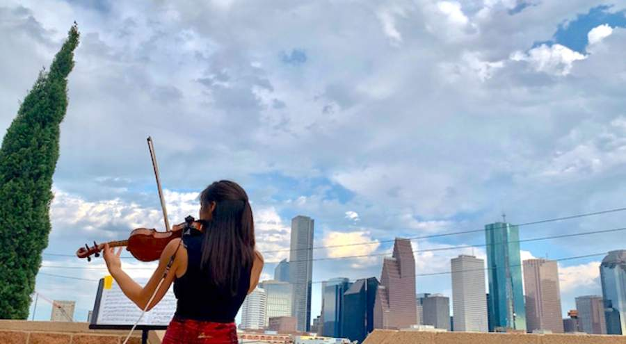 Violinist Mayu Greenhalgh performs from artist Allan Rodewald's rooftop patio at a drive-by art exhibit held in First Ward. (Courtesy Amber Slaughter)