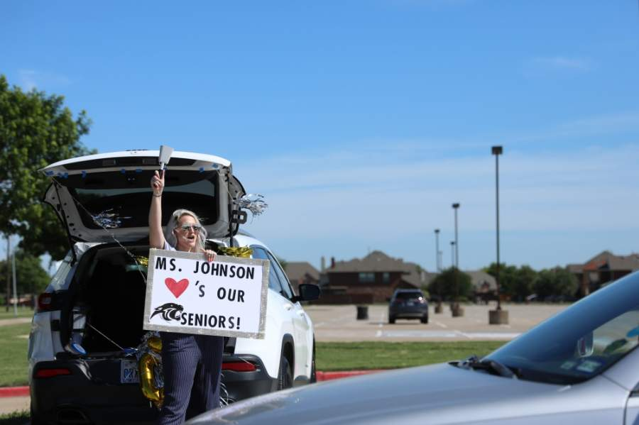 Erica Johnson, a member of the science department at Plano East Senior High, celebrates seniors passing by waving her sign and cowbell in the air at the yard sign pickup May 1. (Liesbeth Powers/Community Impact Newspaper)