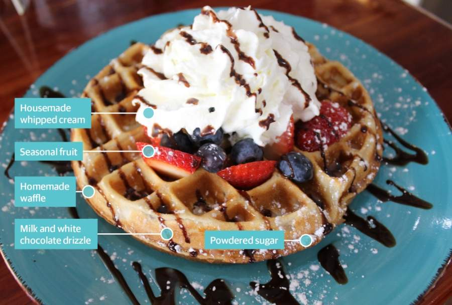 The Awfley Waffley ($9.99) is a homemade waffle topped with fresh seasonal fruit and housemade whipped cream, drizzled with milk and white chocolate and dusted with powdered sugar. (Hannah Zedaker/Community Impact Newspaper)