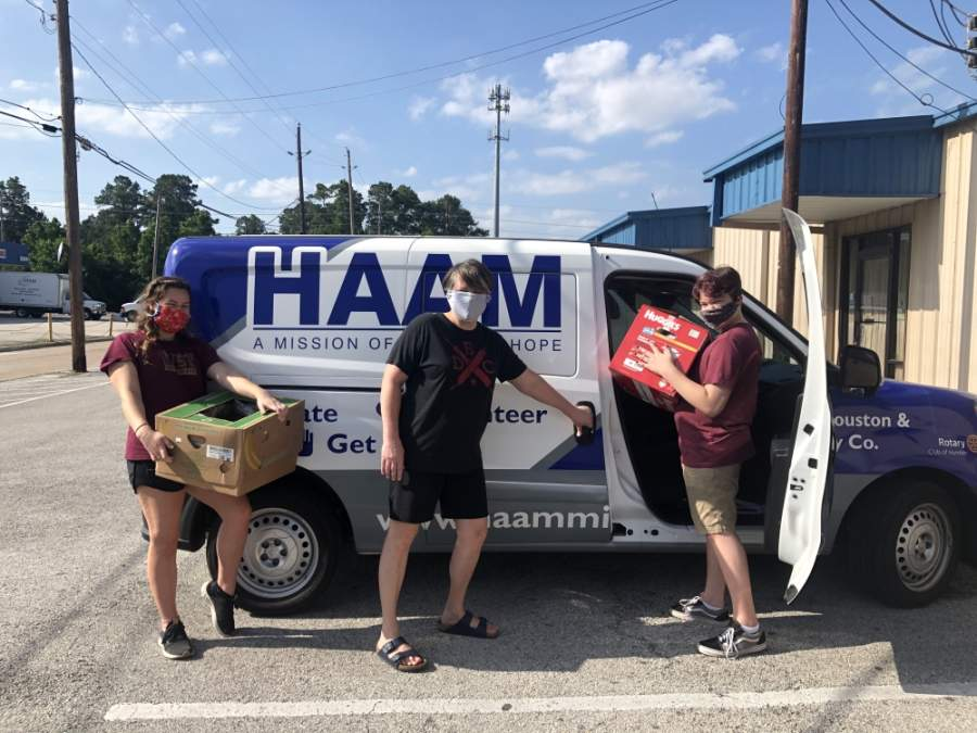 The Costello family loads food packs into a Humble Area Assistance Ministries van for distribution. (Courtesy Humble Area Assistance Ministries)