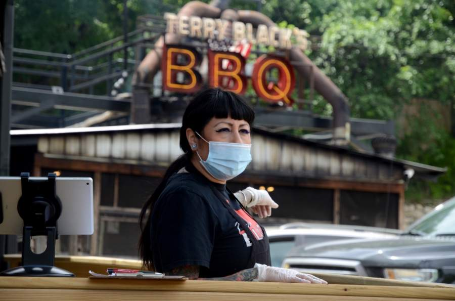 An employee at Terry Black's BBQ in South Austin wears a protective face covering during the restaurant's first day open on May 1. (John Cox/Community Impact Newspaper)