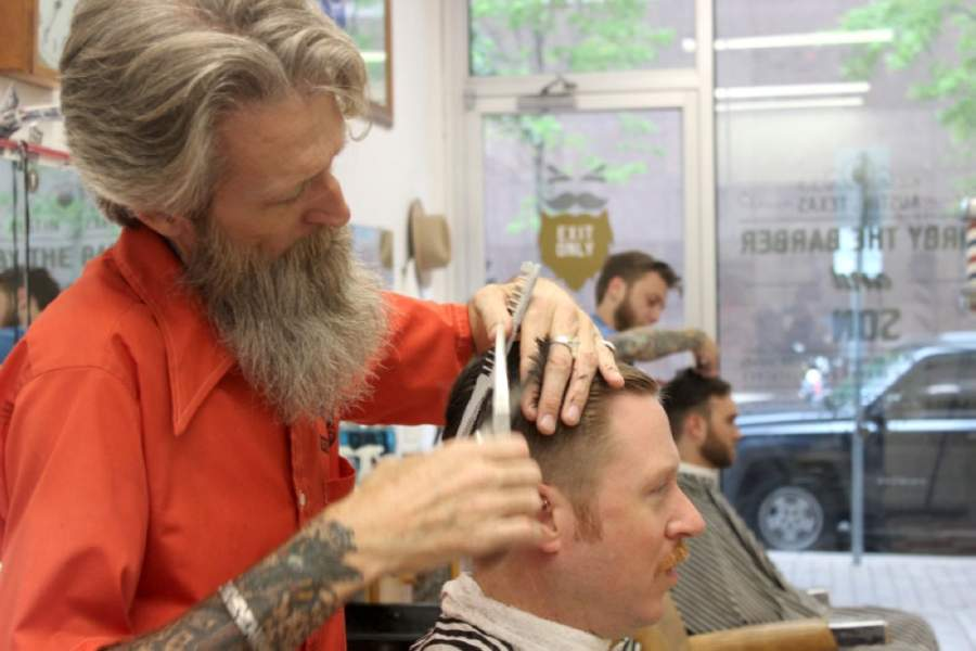 Kirby Schimmels Sr. cuts hair at his downtown barbershop in 2019. When Kirby the Barber reopens May 11, he will cut hair out of a new shop at his Hyde Park home, while his son, Kirby Schimmels Jr., will work downtown. (Jack Flagler/Community Impact Newspaper)