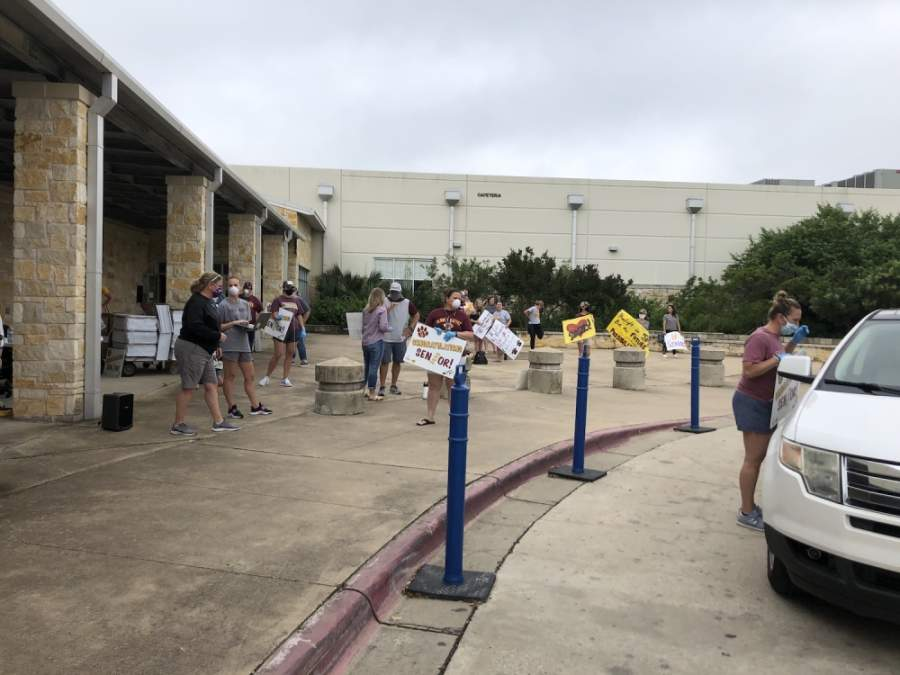 A photo of DSHS staff holding signs to give to seniors outside the high school