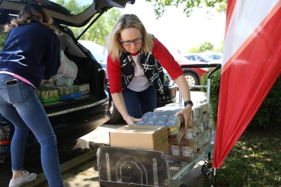 Mimi Conner (right) unloads food from her car after picking up nonperishable foods from the North Texas Food Bank and purchasing foods from Aldi, with help from volunteer Michelle Leavitt. (Liesbeth Powers/Community Impact Newspaper)