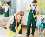 A photo of three people cleaning a living room