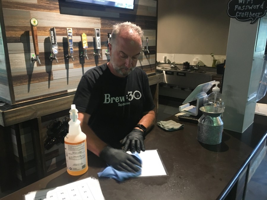 Gary Marler, owner of Brew:30 Taphouse in Cypress, sanitizes a bingo card in preparation for bingo night the taphouse will host June 4. Brew:30 is one of several Cy-Fair bars that reopened in late May under new social distancing guidelines intended to slow the spread of the coronavirus. (Shawn Arrajj/Community Impact Newspaper)