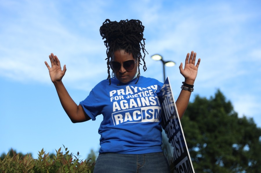 "Many of those present at the gathering of Collin County Churches wore shirts and held signs that said ""praying for justice and against racism."" More shirts with the same message were handed out to the crowd. (Liesbeth Powers/Community Impact Newspaper)"