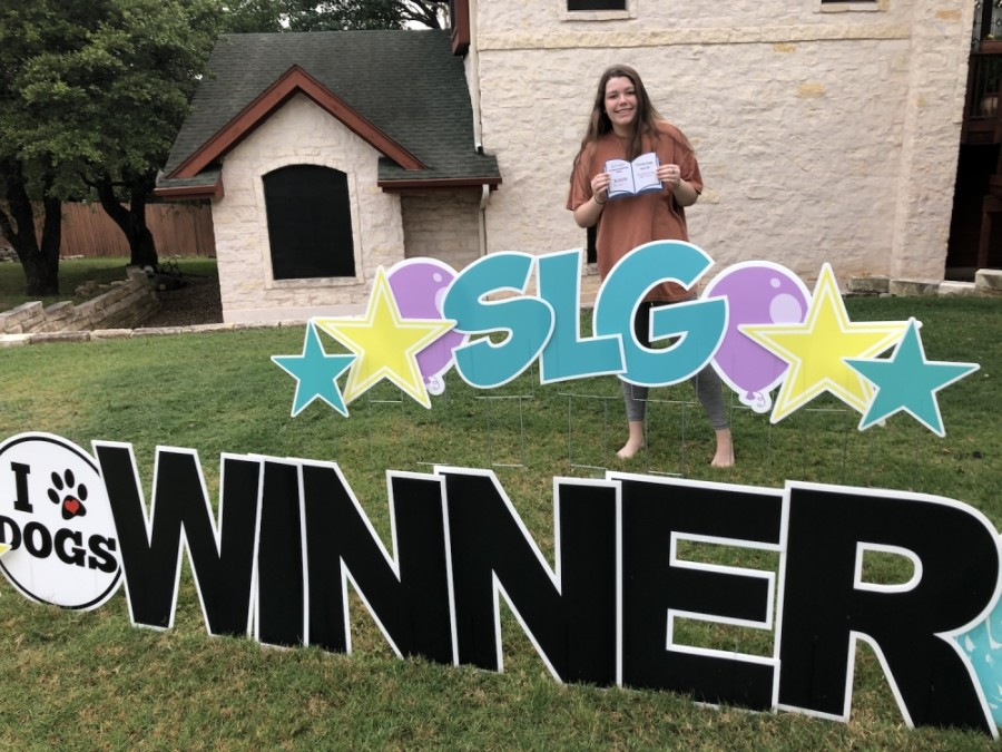 """A photo of a student, Kaylin Whitaker, holding up a check behind a yard sign that reads """"SLG Winner."""""""