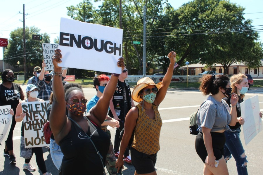 Protesters held signs and chanted as they walked down West Main Street on June 13. (Anna Lotz/Community Impact Newspaper)