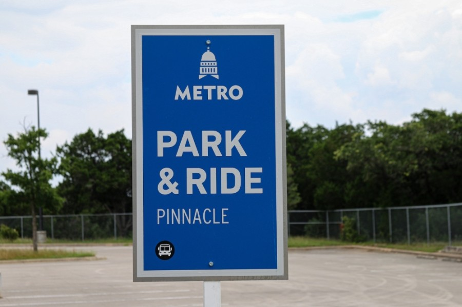 """A photo of a blue sign in a parking lot that reads """"Park & Ride Pinnacle"""""""