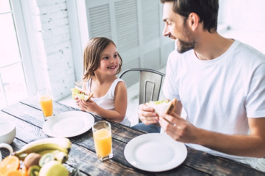 A photo of a dad and daughter eating breakfast together