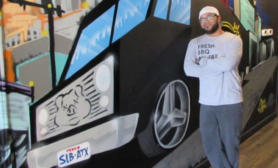 SLAB BBQ & Beer co-owner Raf Robinson stands in front of a mural at the restaurant's Southwest Austin location in 2019. (Nicholas Cicale/Community Impact Newspaper)