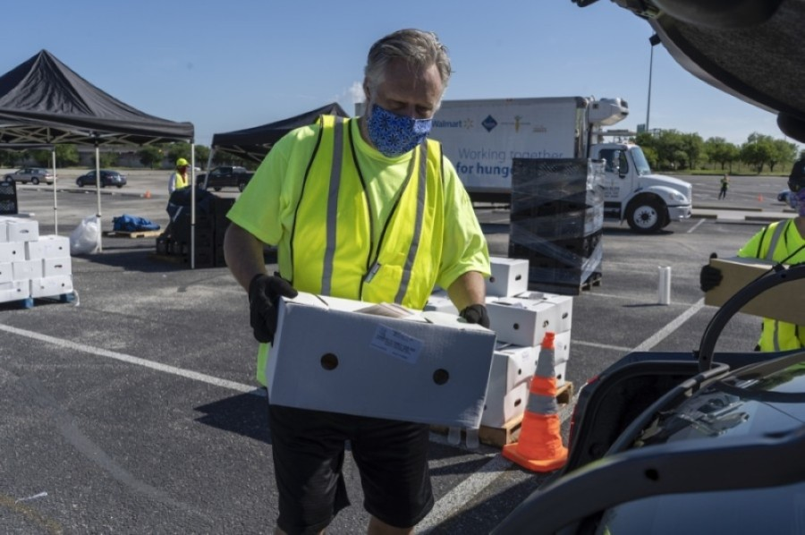 A volunteer loads food into a a car during a Central Texas Food Bank distribution event at the Toney Burger Center in South Austin. (Courtesy Central Texas Food Bank)