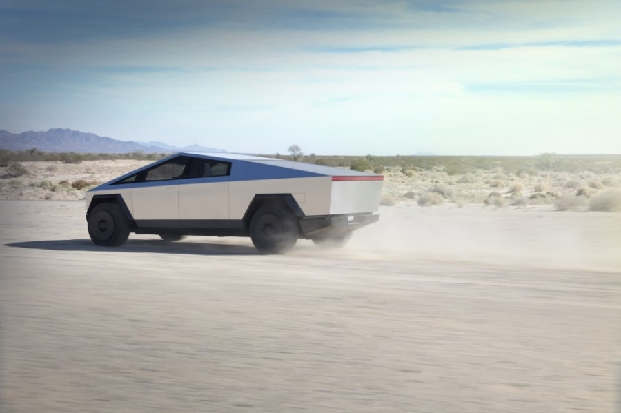 A photo of a silver Cybertruck zooming through the desert