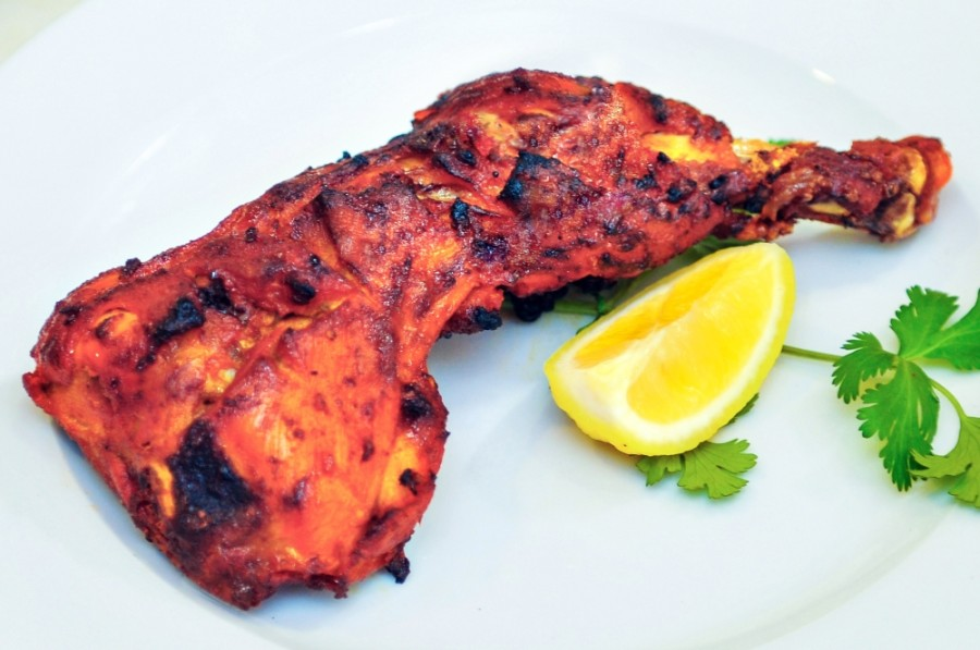 Tandoori chicken with a lemon slice and stem of cilantro, served on a plate
