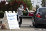 Pharmacist Emily Smith opens a cooler for a patient to place their self-swab coronavirus test at a Walmart drive-thru testing site in McKinney on June 29. (Shelby Tauber/The Texas Tribune)