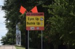 "A photo of a road sign that reads, ""Eyes Up; Buckle Up."""