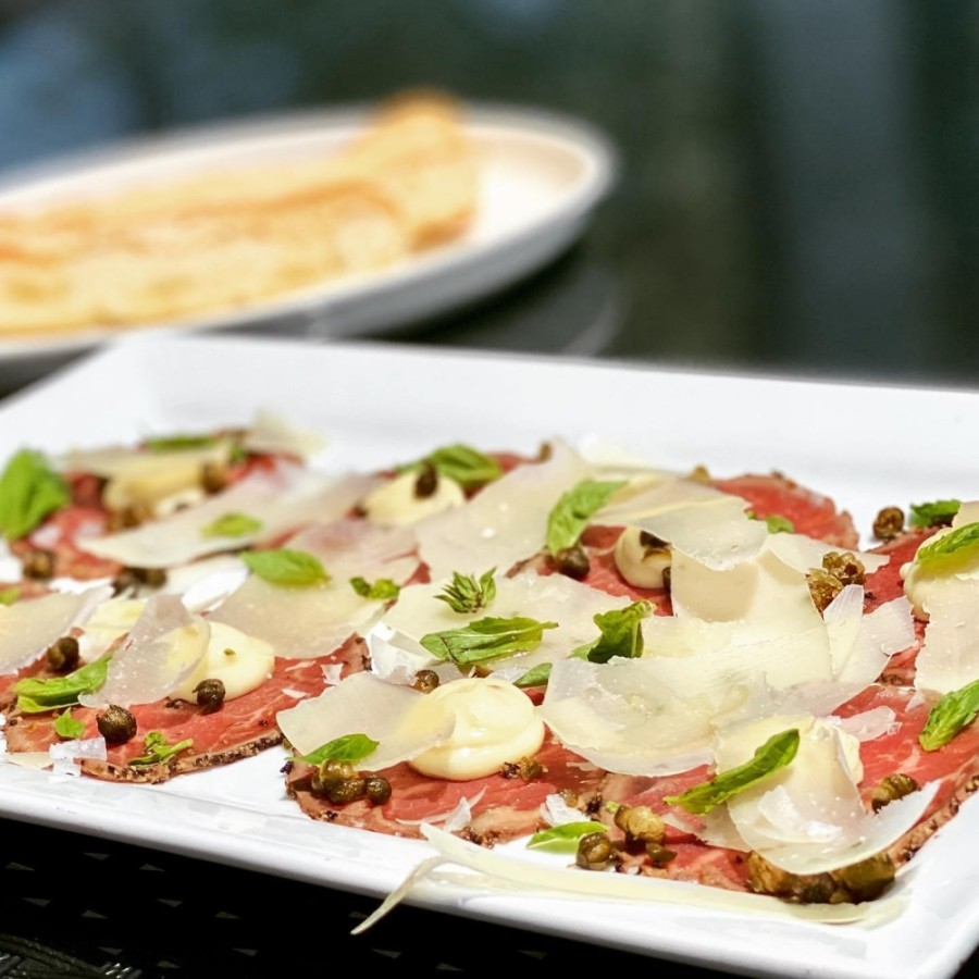 Carpacio di Manzo consists of black pepper crusted beef carpaccio, shaved parmesan, crispy capers, microgreen basil, truffle aioli and focaccia chips. (Courtesy Avanti Italian Kitchen and Wine Bar)
