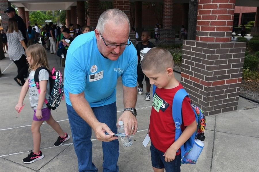 A Cy-Fair ISD volunteer assists a student in finding the right school bus during the Bus Buddies program in 2019. (Courtesy Cy-Fair ISD)