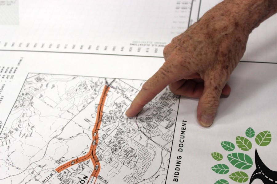 A resident points to a Oak Hill Parkway blueprint at a public open house in 2018. (Taylor Jackson Buchanan/Community Impact Newspaper)