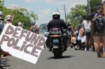 A police officer rides past protesters during the June 7 Justice for Them All March. (Christopher Neely/Community Impact Newspaper)