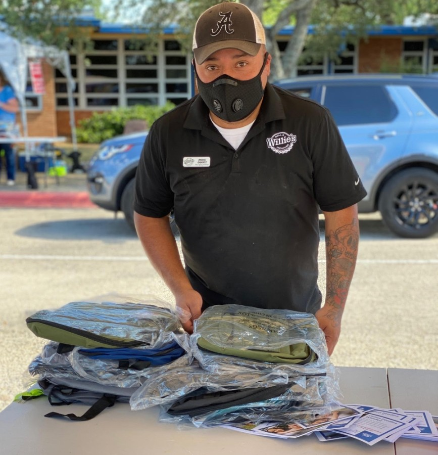 Miguel Ramirez, manager of the Georgetown Willie's Grill & Icehouse, packs backpacks full of school supplies that were given out to about 600 cars Aug. 11 at the Fill the Bus event sponsored by the Georgetown Area Junior Forum. (Courtesy Georgetown Area Junior Forum)