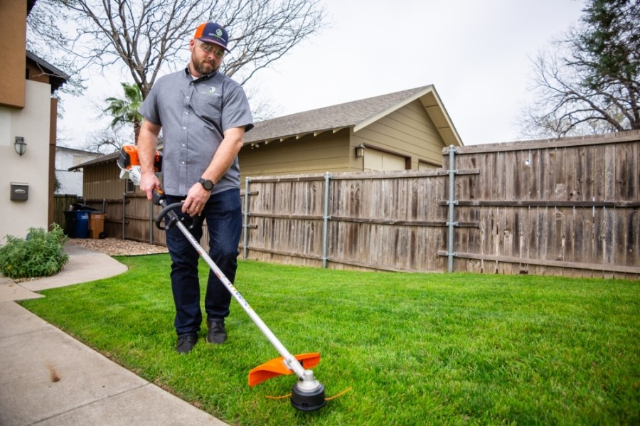 Just Right Lawn owner Jeremy Griffin weed whacks a lawn in South Austin. (Photos courtesy Just Right Lawns)