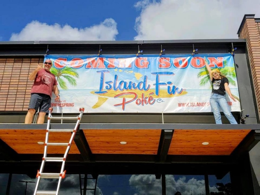 "Franchise co-owner Matt Gustafson (left) and his daughter hang the ""coming soon"" sign for their new Island Fin Poke Co. location in Spring. (Courtesy Matt Gustafson)"