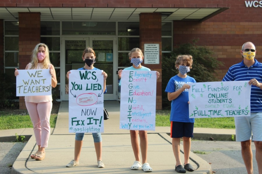 More than two dozen parents and students gathered in Franklin on Sept. 9 and held up signs asking for equal opportunity to learn as school board members walked into the meeting space. (Wendy Sturges/Community Impact Newspaper)